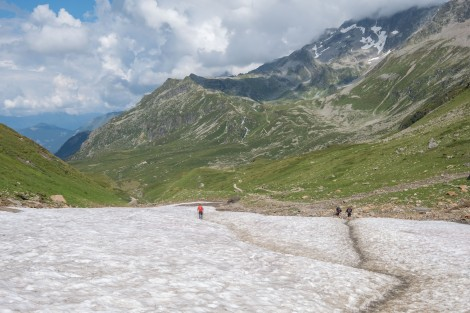 Walking through a snow field after Col du Bonhomme