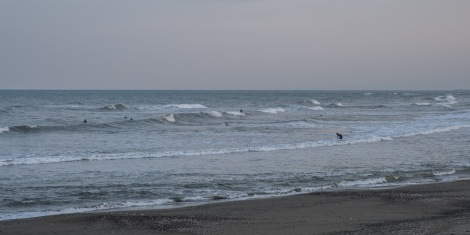 Surfers in Takanabe at dusk