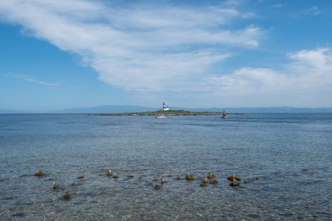 Standing at Cape Oma looking out to a lighthouse on Benten Island with Hokkaido in the background