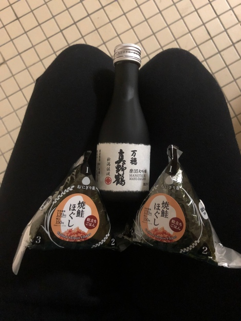 Dinner of rice balls and sake in a toilet block