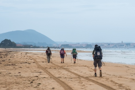 Pilgrims walking along Playa de Noja towards Noja