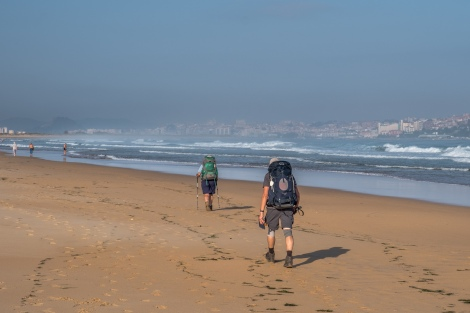 Walking along Playa de Somo with a view of Santander in the background