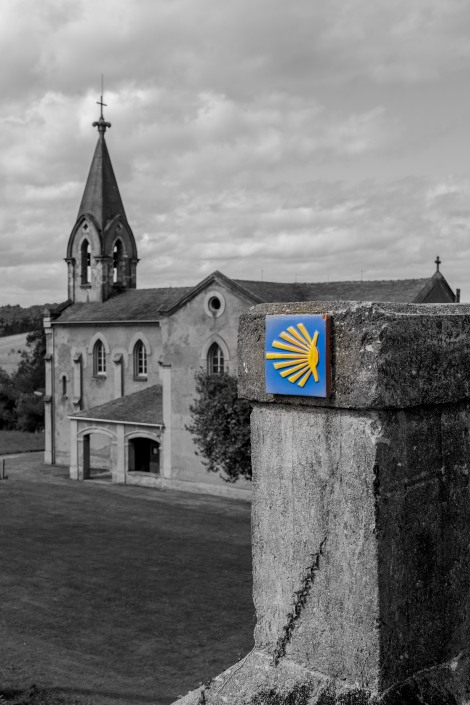 A Camino waymark and the Church of St Saviour (Parroquia de San Salvador) in Piñera