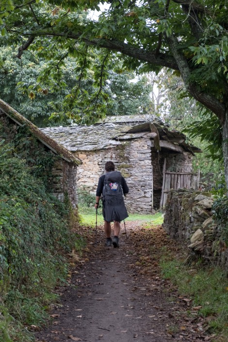 A pilgrim and traditional Galician stone buildings